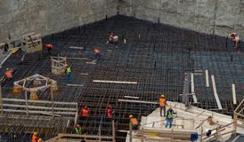Pracownicy przy pracą dla budowy zbrojona betonowa baza obraz royalty free