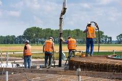 Pracownicy przygotowywa betonową podstawę Holenderski silnik wiatrowy Zdjęcia Stock