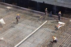 Pracownicy robią wzmacnieniu dla betonowej podstawy zdjęcia royalty free