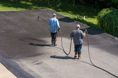 Pracownicy rozpyla blacktop lub asfaltu sealer na jezdni obrazy royalty free