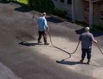 Pracownicy rozpyla blacktop lub asfaltu sealer na jezdni zdjęcie stock