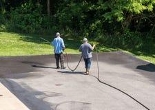 Pracownicy rozpyla blacktop lub asfaltu sealer na jezdni zdjęcia royalty free