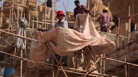 Pracownicy są wspinający się starą ceglaną pagodę i naprawiający zbiory