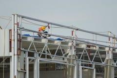 Pracownicy w kosze instalują prześcieradło, buduje fabrykę Fotografia Stock