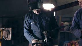 Pracownicy w ochronnym workwear przy machinalnym hangarem Robociarz w spawalniczym hełmie łączy dwa metalu kawałka wpólnie zbiory