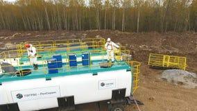 Pracownicy w stroju spojrzeniu w ląg na zbiorniku z substancjami chemicznymi brzoza lasem zbiory