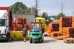 Pracownicy z forklifts w magazynie plastikowe drymby Sprzedaż materiały dla budowy i ulepszać terytorium industr fotografia stock