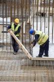 Pracownicy z piętakiem usuwają drewnianych formworks Fotografia Stock