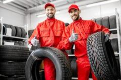 Pracownicy z samochodowymi oponami przy magazynem fotografia royalty free