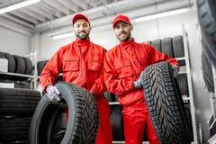 Pracownicy z samochodowymi oponami przy magazynem zdjęcia royalty free