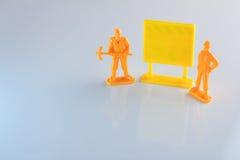 Pracownicy zabawkarscy i pusty żółty signage jpg Zdjęcie Royalty Free