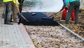 Pracownicy zrównują kruszkę asfalt w jamie z rolownikiem przed brukowaniem z drogowym mini budynku rolownikiem Bi obrazy stock