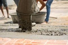 Pracowniczy dolewanie cement na ziemi dla budowy nowej podłoga dla renov Zdjęcia Stock