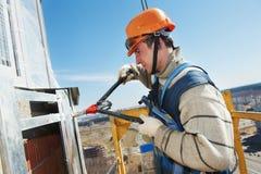 Pracowników budowniczowie przy fasady płytki instalacją Zdjęcia Royalty Free