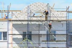Pracowników budowniczych dźwignięcia materiały budowlani na rusztowaniu Fotografia Royalty Free