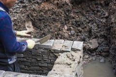 Pracownik budowlany będący ubranym błękitnych kombinezony trzyma chusteczkę w drenażowym przykopie fotografia stock