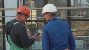 Pracownik budowlany i inżynier opowiada przy budowy miejscem, tylni widok zbiory