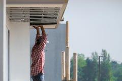 Pracownik budowlany instaluje podsufitow? desk?, zewn?trzna budowa zdjęcia royalty free