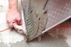 Pracownik budowlany jest tafluje w domu dachówkowej podłoga zdjęcia stock