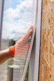Pracownik budowlany jest ubranym w rękawiczkach i instaluje specjalną siatkę na okno Budowy apretury pracy Obraz Royalty Free