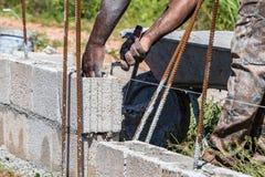 Pracownik budowlany, kamieniarz, murarz kłaść cementu blok/ obraz stock