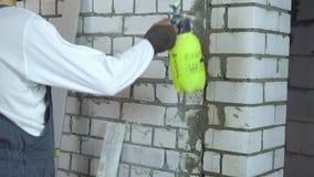 Pracownik budowlany moisturing ściana z cegieł z wodną natryskownicą zbiory wideo