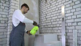 Pracownik budowlany moisturing wietrzących betonowych bloki z wodną natryskownicą zdjęcie wideo