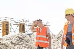 Pracownik budowlany patrzeje zmęczonego kolegi obcierania pot przy miejscem obraz stock