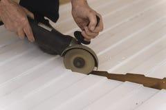 Pracownik budowlany piłuje stalowego prześcieradło z trapezoidalnym profilem zdjęcie stock