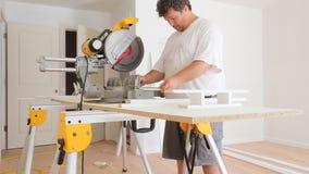 Pracownik budowlany przemodelowywa domowego cieśli ciie drewnianą podstrzyżenie deskę z kółkowym saw dalej zdjęcie wideo
