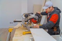 Pracownik budowlany przemodelowywa domowego cieśli ciie drewnianą podstrzyżenie deskę z kółkowym saw dalej obrazy stock