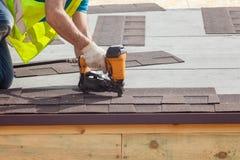 Pracownik budowlany stawia asfaltowego dekarstwa gonty z gwoździa pistoletem na nowym ramowym domu zdjęcia stock