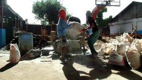 Pracownik Budowlany stawia torbę cement w betonowym melanżerze w budować budynek szkoły zbiory wideo