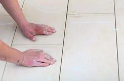Pracownik budowlany tafluje w domu, dachówkowa podłoga adhezyjna Zdjęcie Stock