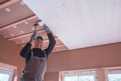 Pracownik budowlany thermally izoluje eco drewnianego ramowego dom Zdjęcie Stock