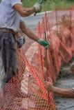 Pracownik budowlany ustawiający pomarańczowy zbawczy ogrodzenie Obrazy Royalty Free