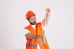 Pracownik Budowlany w Zbawczym hełmie jest Pomiarowy z metrem Zdjęcia Royalty Free