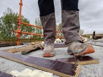 Pracownik budowlany wypadek przez miejsca z gruzami i kroczenia na gwo?dziu podczas gdy spacery obrazy stock