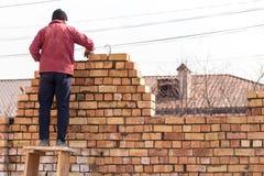 Pracownik buduje ściana z cegieł w domu obraz stock