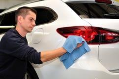 Pracownik czyści samochód. Obrazy Royalty Free