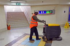 Pracownik czysta podłoga z cleaning skruberu podłogową maszyną Obraz Stock