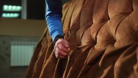 Pracownik dociska tkaninę na ścierwie kanapa, zakończenie zbiory wideo