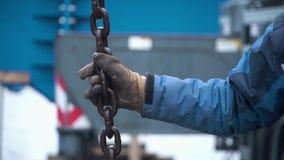 Pracownik dotyka dźwigowych haczyki pętle podczas remontowej pracy klamerka Pracownik utrzymuje łańcuch żuraw zbiory