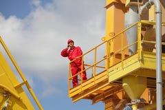 Pracownik dzwoni na telefonie na przemysłowej platformie w mundurze Zdjęcie Royalty Free