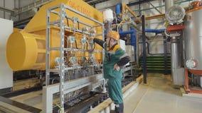 Pracownik egzamininuje ciśnieniowych metry przy benzynowymi zbiornikami zbiory