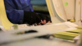Pracownik fabryczny dla produkci samoloty dociska dokrętki z wyrwaniem, widok kadłub from inside zbiory