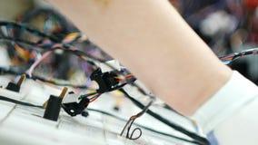 Pracownik fabryczny ręki pracują na maszynowych i łączą elektrycznych drutach zbiory