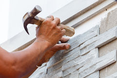 Pracownik instaluje kamiennej ściany powierzchnię z cementem dla domu Zdjęcie Stock