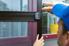 Pracownik instaluje komar sieci drutu parawanowych drzwi obraz royalty free