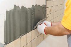 Pracownik instiling płytki na ścianie w kuchni zdjęcie royalty free